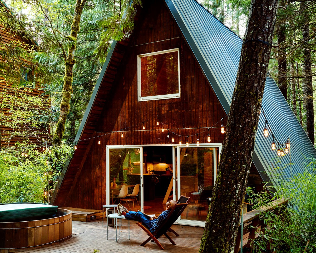 A man sits outside an A-frame house deep in the woods in Washington State.