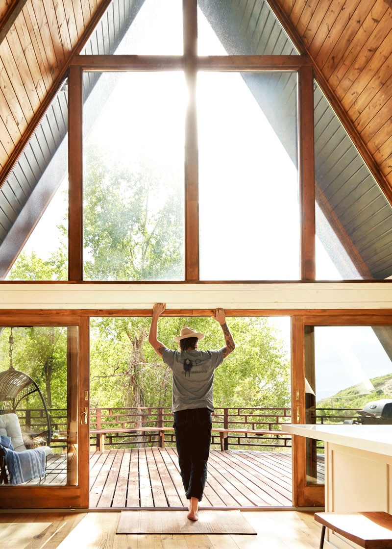 A person leans on the frame of an A-frame house in Heber, Utah.