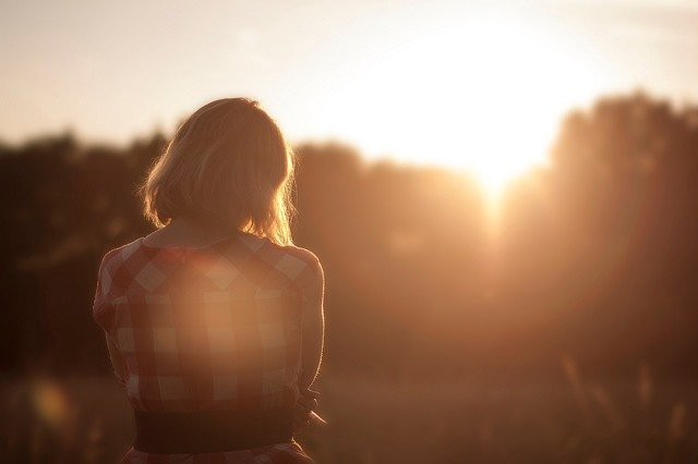 A woman watches the sun set