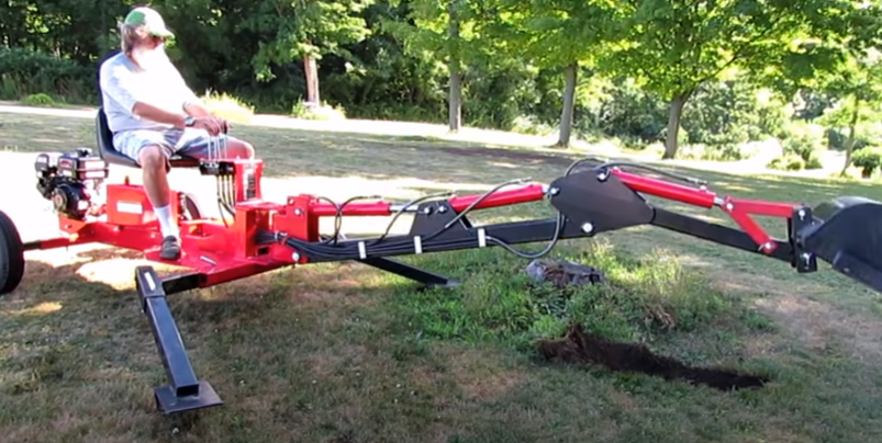 man using towable backhoe for landscaping