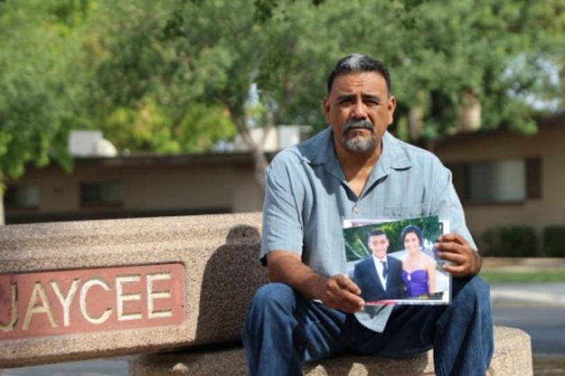 Adrienne Salinas?s father Rick sitting at Jaycee Park in Tempe, Ariz., showing a picture of his murdered daughter.
