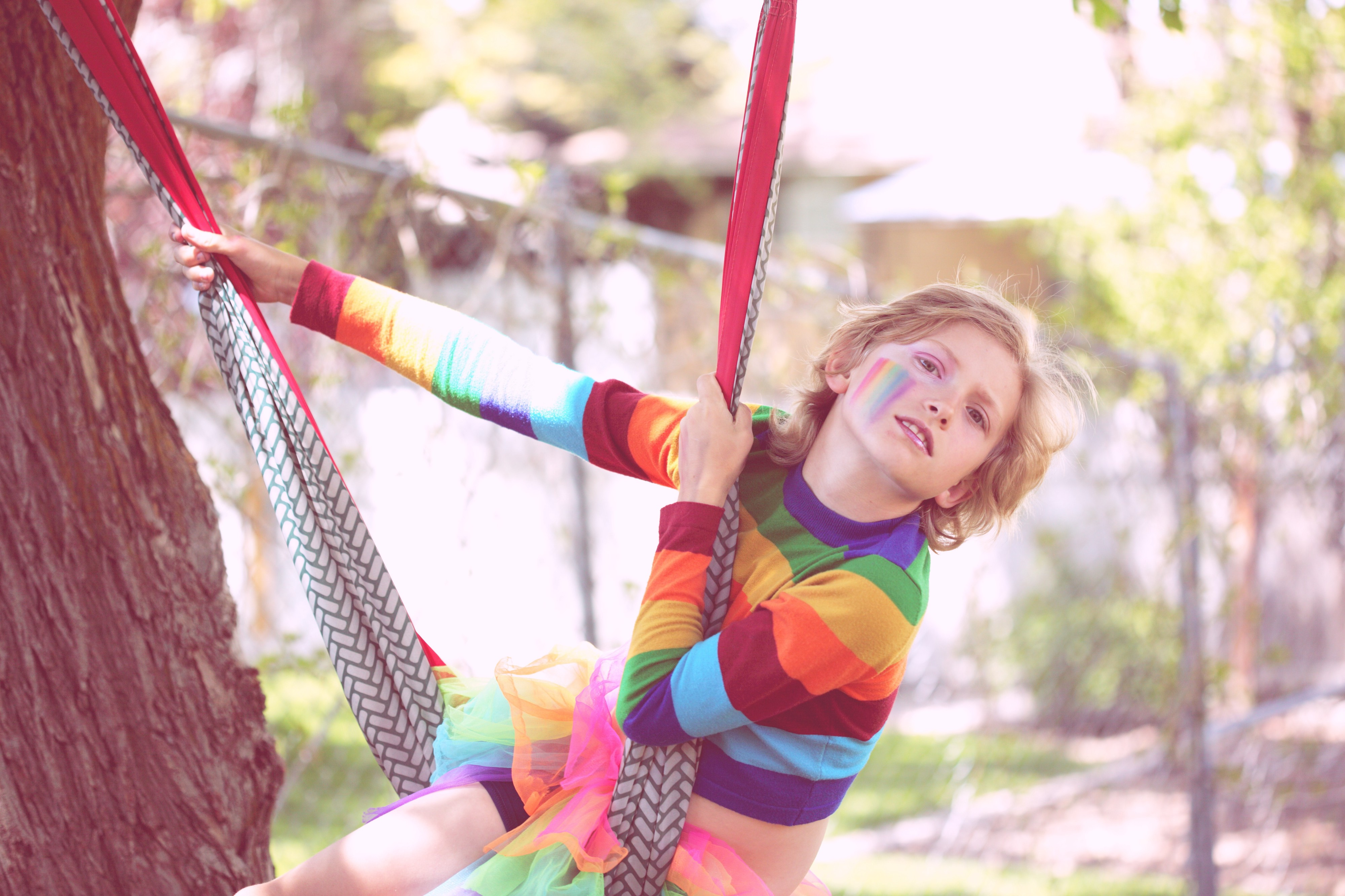 A kid in a rainbow striped sweater and rainbow tutu, with rainbow face paint, plays on a hammock swing outside