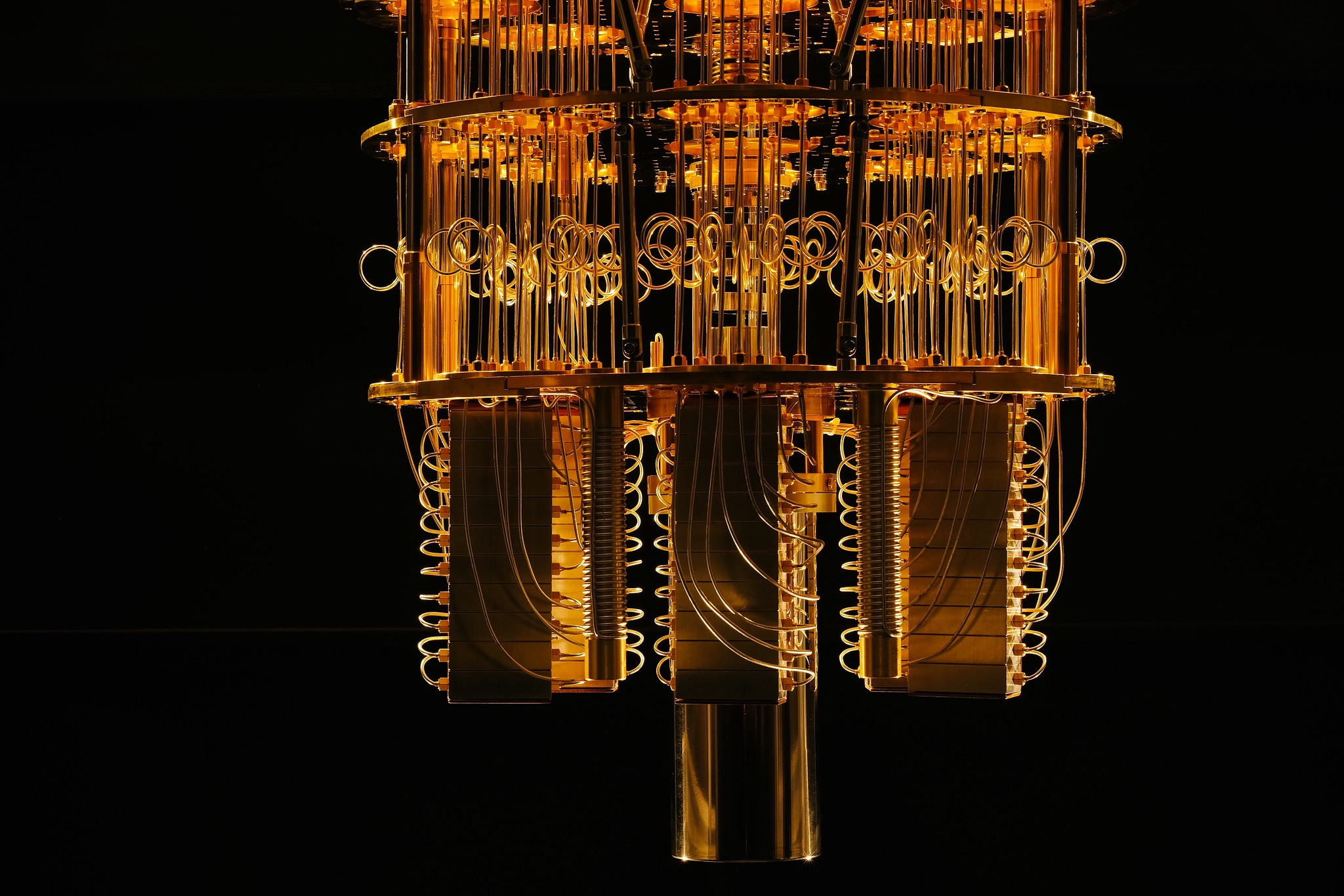 A dramatic photograph of the IBM quantum computer?s wire-filled chandelier on a black background