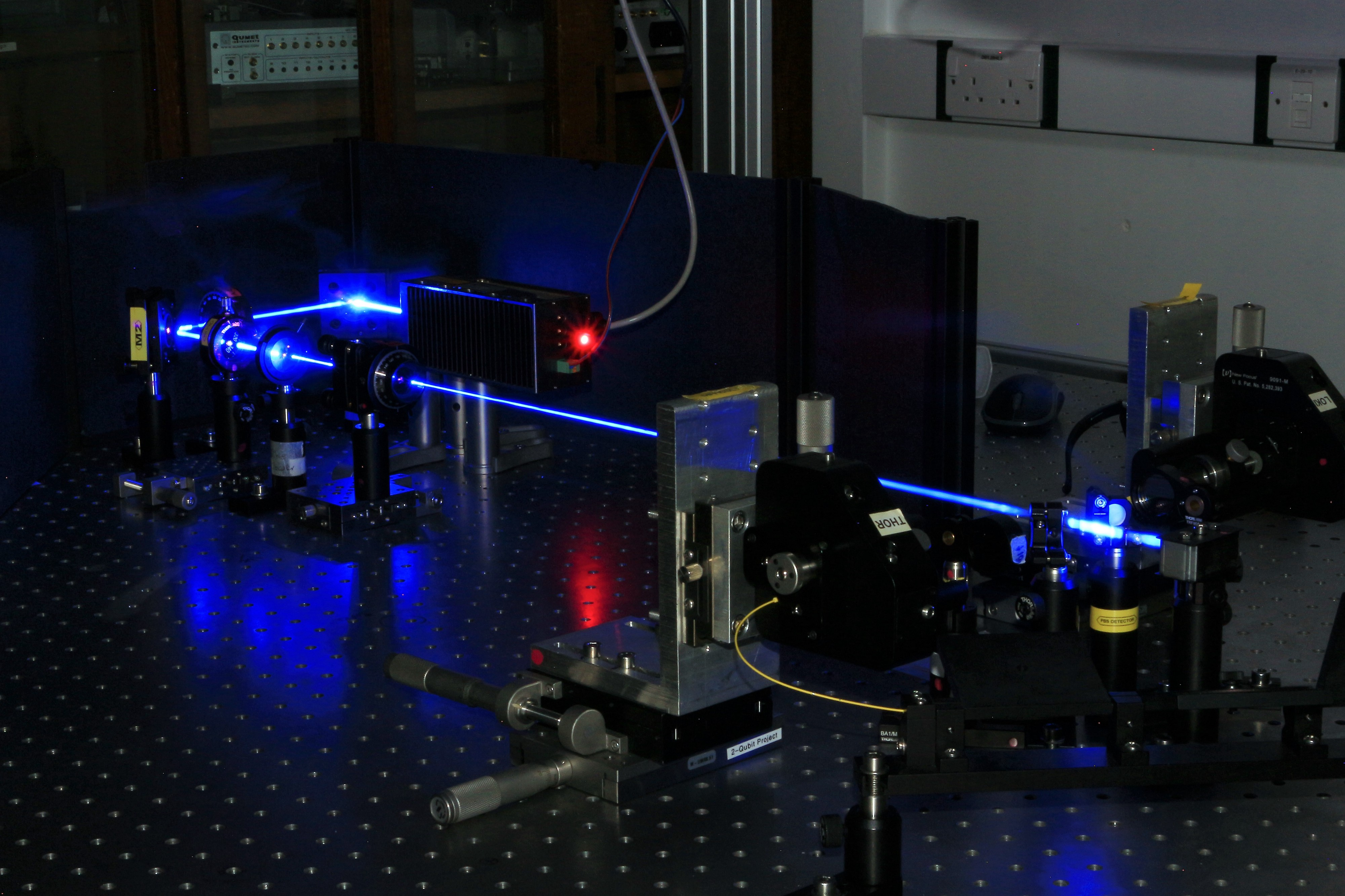 A table with a laser beam passing through optical equipment