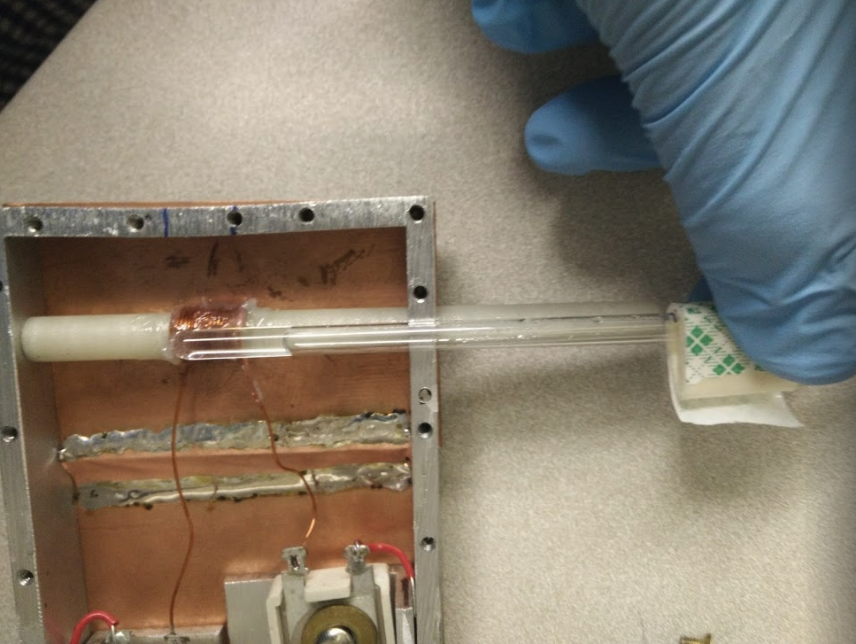 A gloved hand holding a small vial of water next to a simple, homemade NMR device
