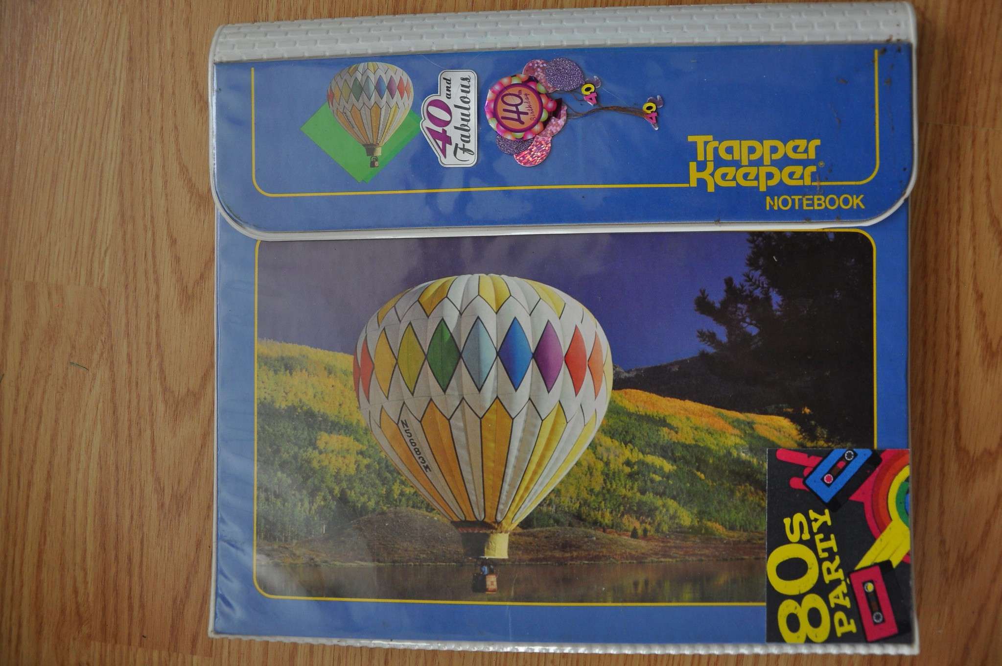 Blue Trapper Keeper notebook with hot air balloon and cassette tape with 80s party in bottom right corner.