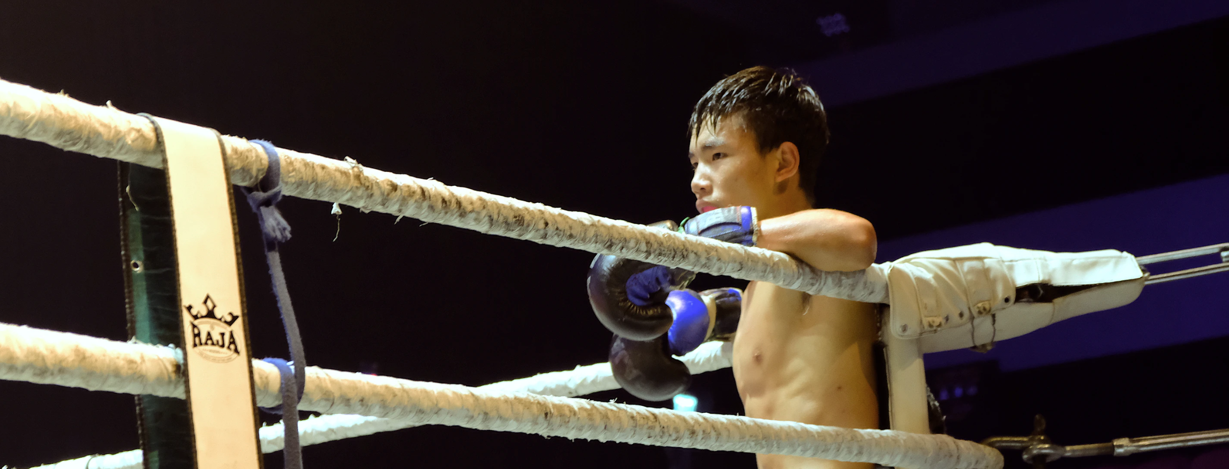 A young Muay Thai practitioner waiting for the bell in his corner