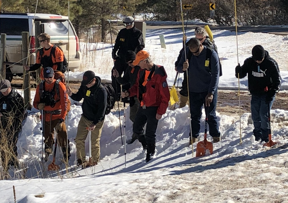Search crews with long poles and shovels search in the snow on South Perry Park Road.