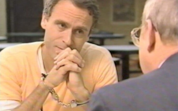Ted Bundy speaking with an investigator while on death row in 1989, at Florida State Prison.