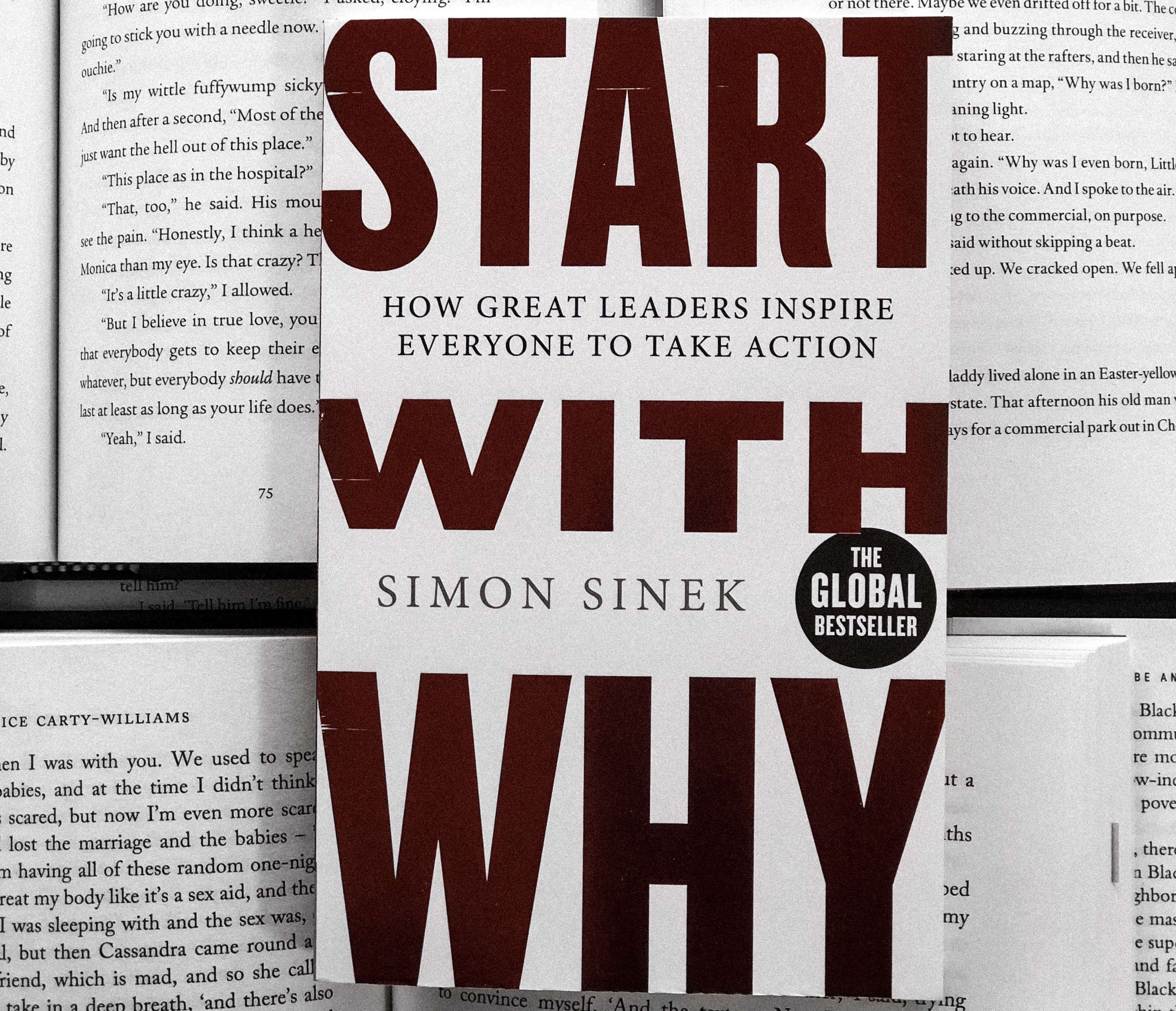 The print of Start With Why by Simon Sinek placed on top of several opened books.