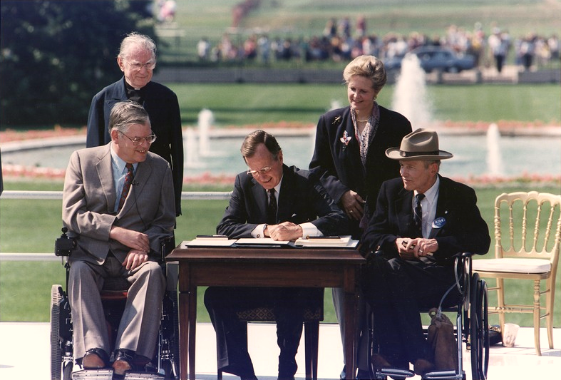 George H. W. Bush signing the Americans with Disabilities Act outside surrounded by two men in wheel chairs and two others.