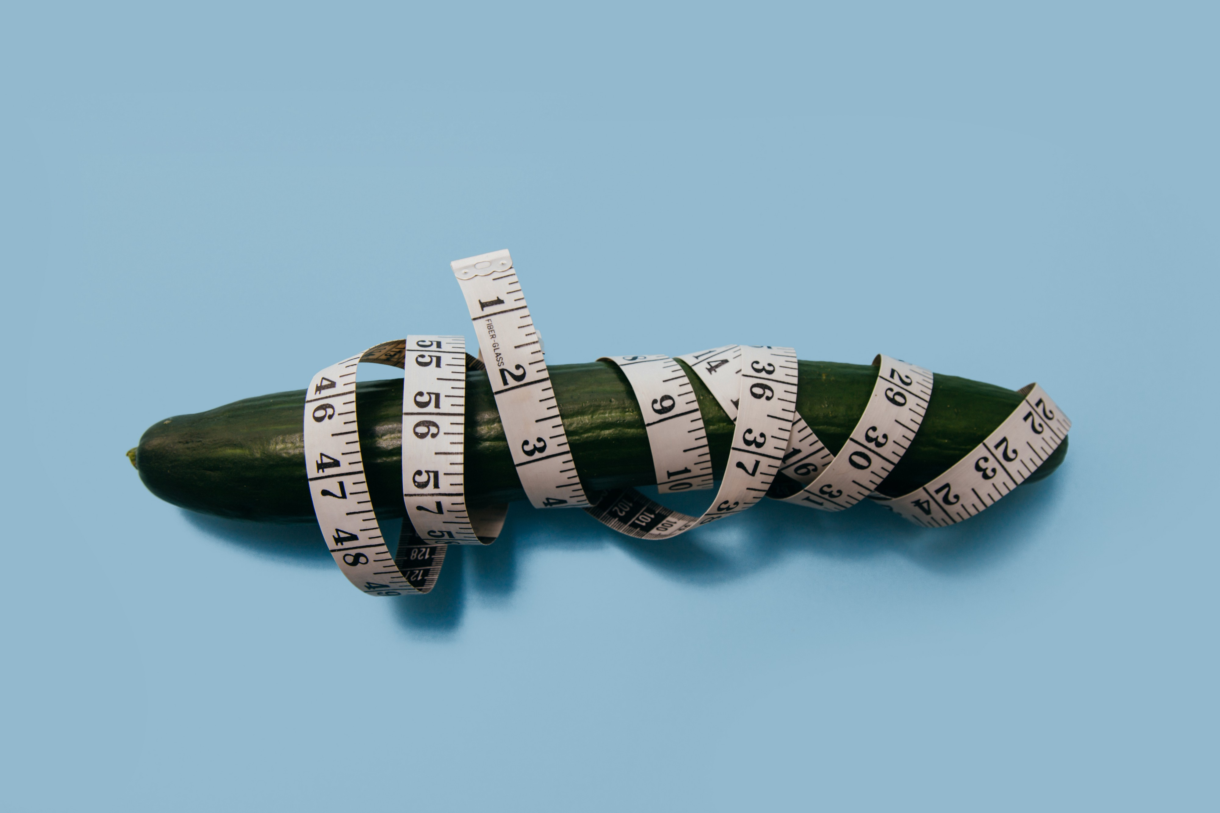 Photo of a sad-looking, wilty cucumber wrapped in a tape measure