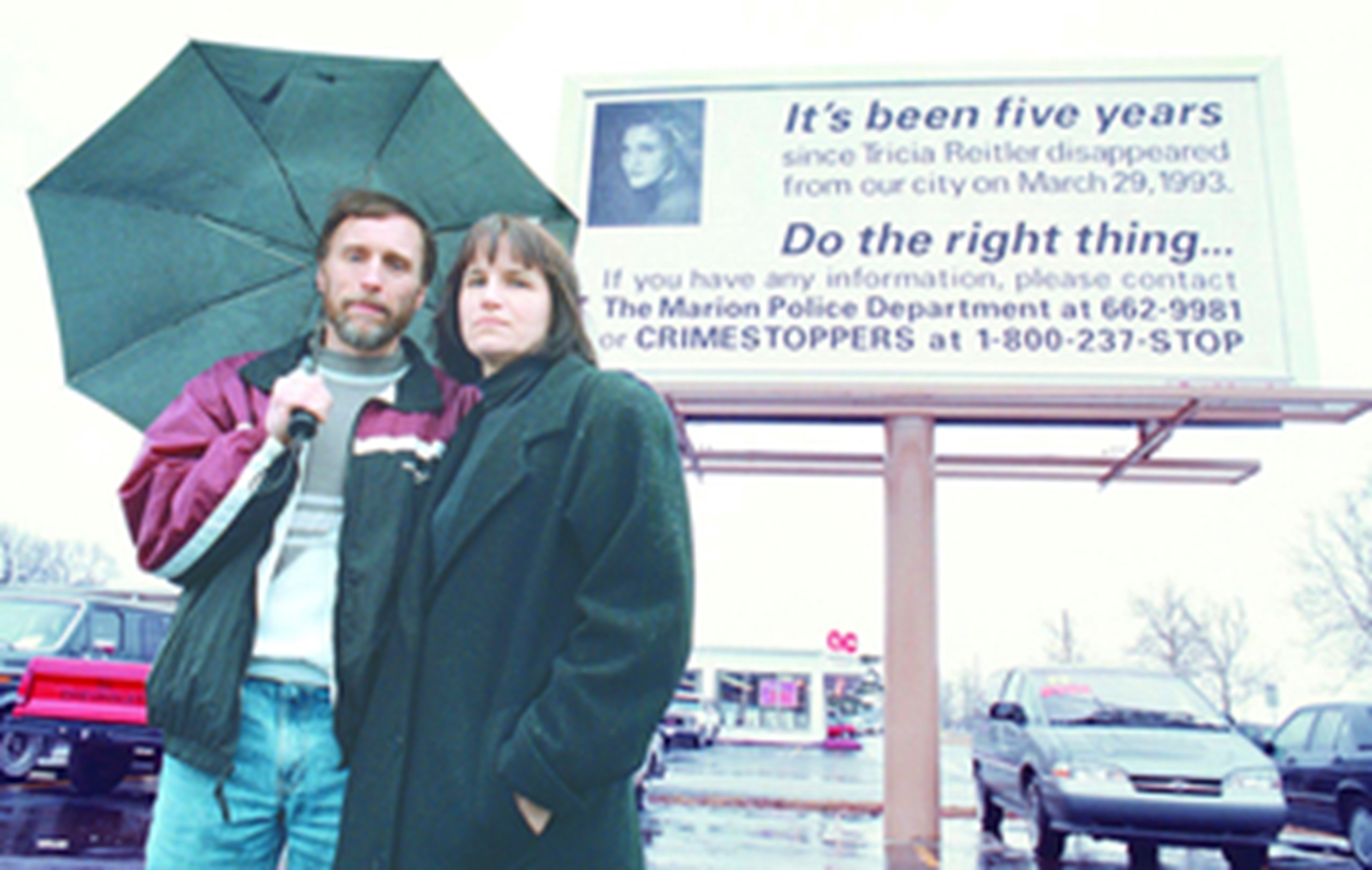 Tricia Reitler?s parents Garry and Donna standing in front of a billboard on 41st Street and Western Avenue.