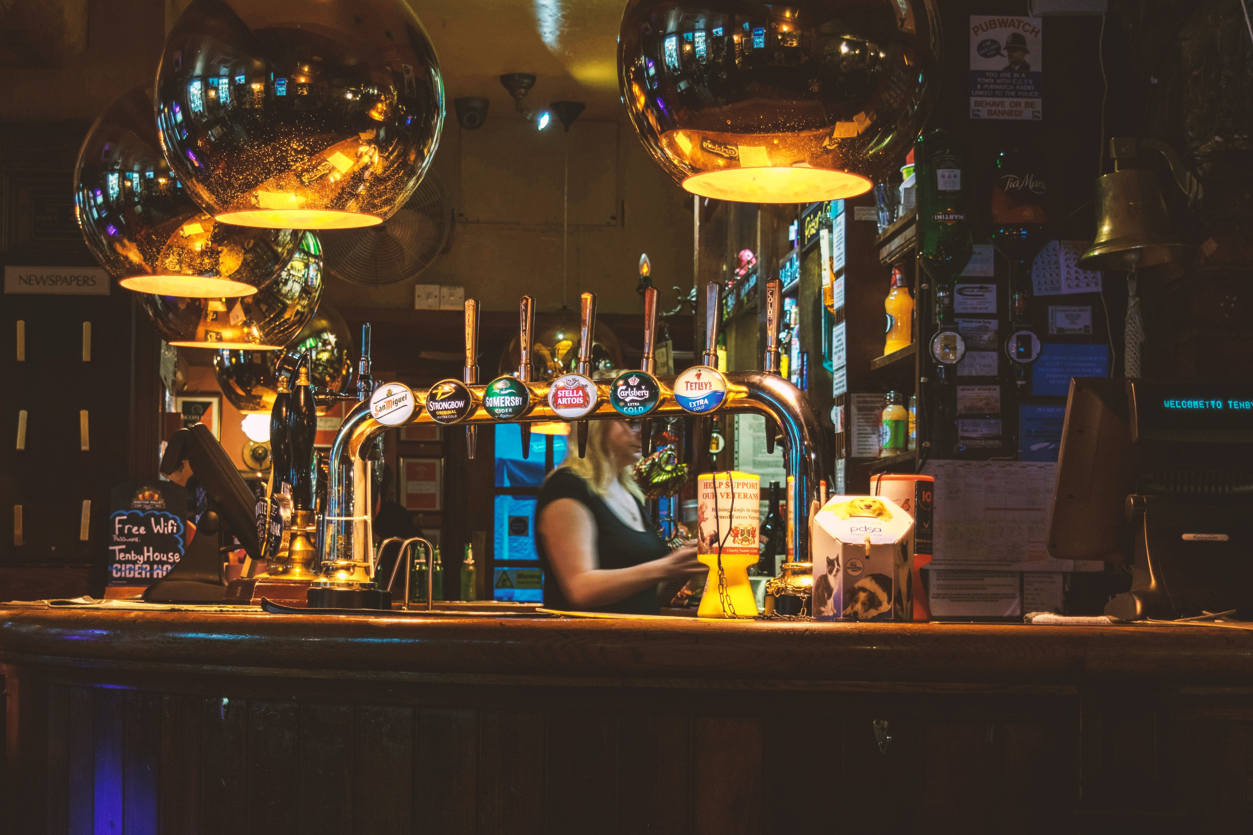 Blonde woman behind a bar with beer taps.