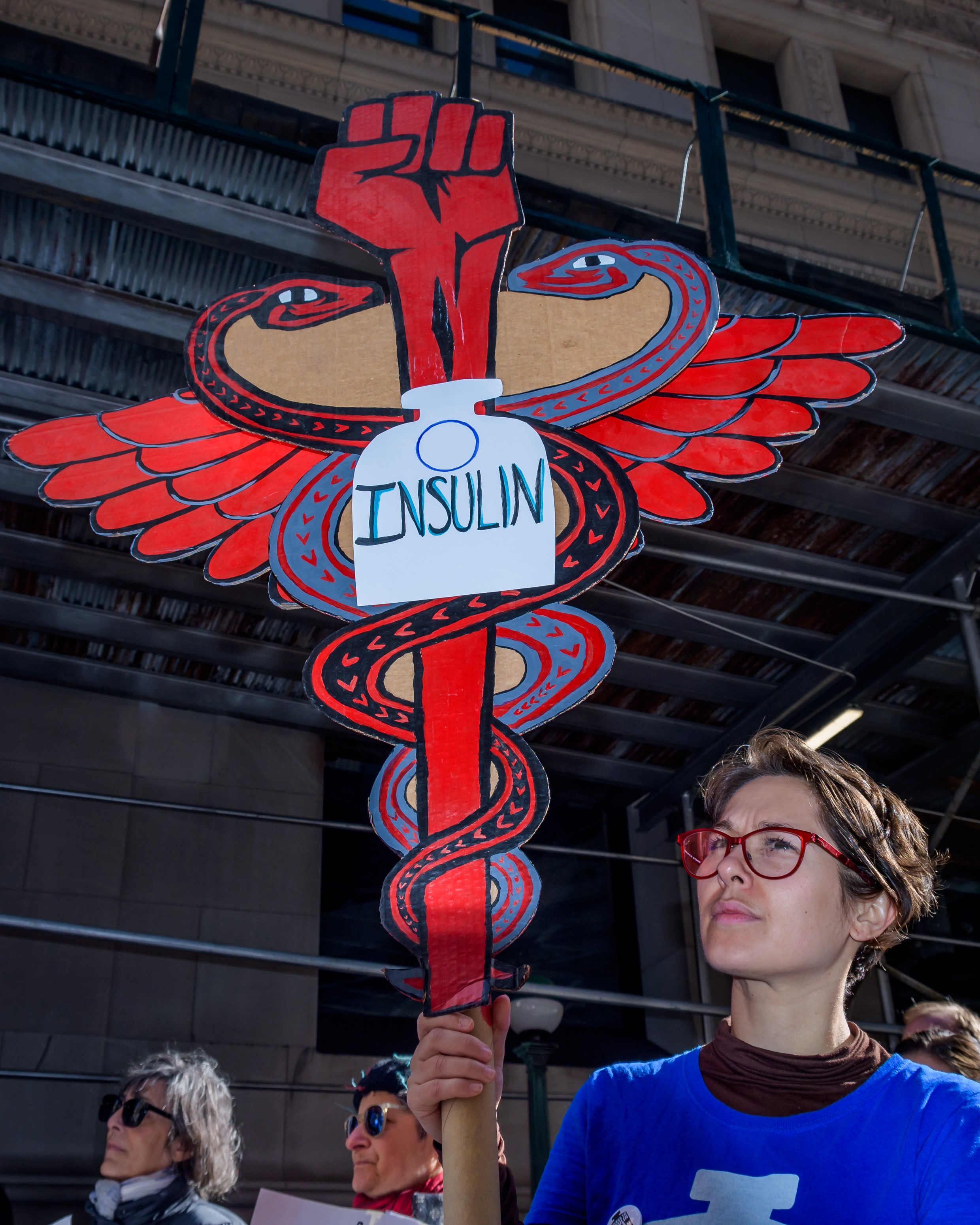 Participant holding a protest sign at a rally for affordable insulin for people with diabetes.