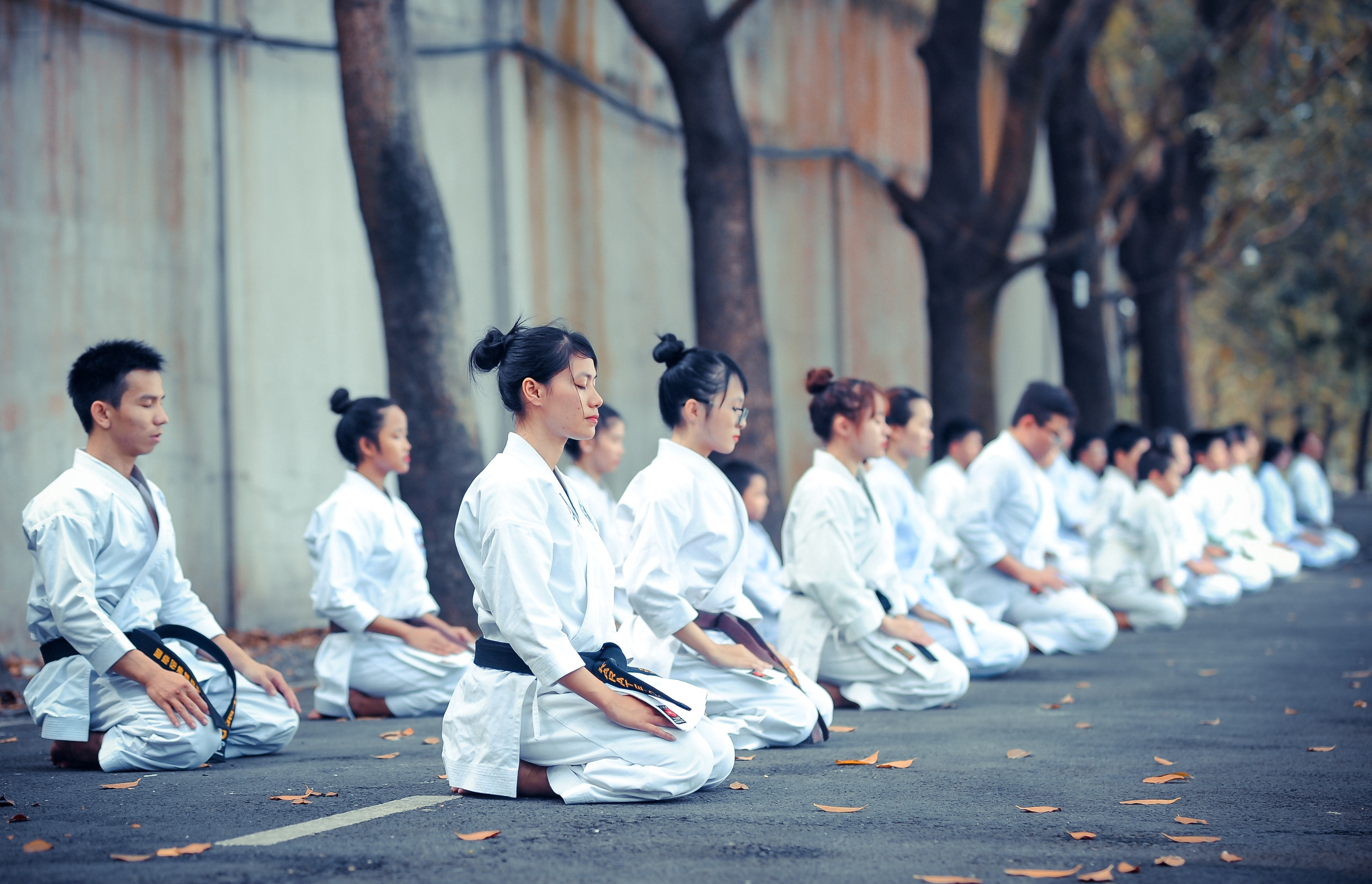 Young Karate students sitting on the street and meditating